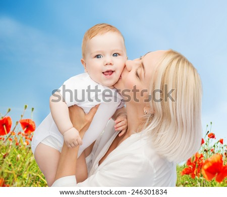 people, family, motherhood and children concept - happy mother hugging adorable baby over blue sky and poppy field background - stock photo