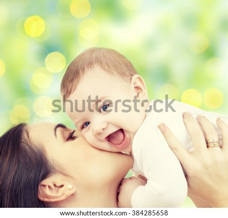 people, family, motherhood and children concept - happy mother hugging adorable baby over green lights background - stock photo