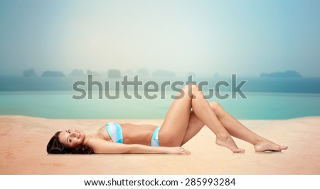 people, fashion, swimwear, summer and travel concept - happy young woman lying and tanning in bikini swimsuit