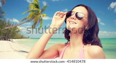 people, fashion, tourism, travel and summer concept - happy young woman in sunglasses and pink swimsuit looking up over tropical beach background