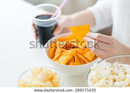 people, fast food, junk-food and unhealthy eating concept - close up of woman with popcorn, nachos or corn crisps and peanuts in bowls - stock photo