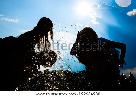 People feeling free in the sunset having a summer party in the water - stock photo