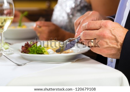 People fine dining food at table in hotel or elegant restaurant