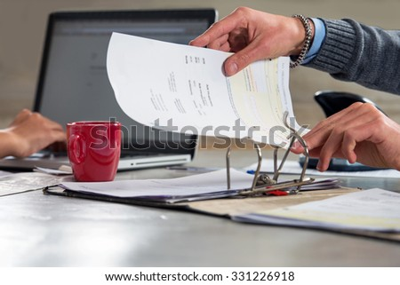 People, fining documents and doing their administration, working on a laptop and filing invoices and bills in a ring binder, archiving them for tax returns - stock photo