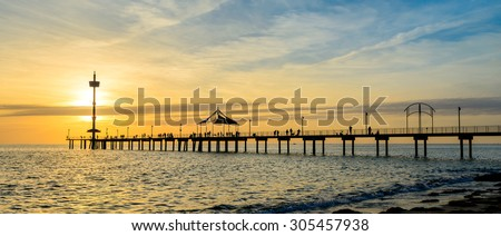 People fishing and walking on the Brighton jetty at sunset - stock photo