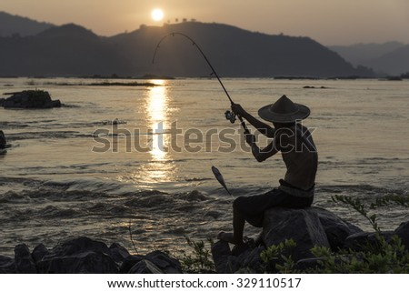 People fishing on the Mekong River at sunset .