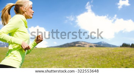 people, fitness, sport and healthy lifestyle concept - happy sporty woman running or jogging over nature