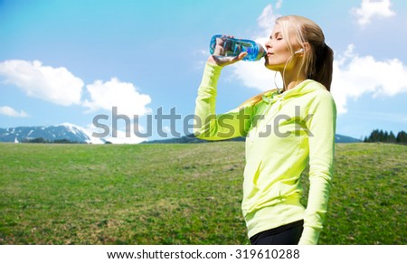 people, fitness, sport and healthy lifestyle concept - happy woman drinling water from bottle after workout over natural background - stock photo