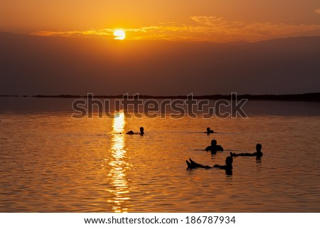 People floating at the Dead sea at dawn, Israel . The Dead Sea is a salt lake in Israel. Its shores are the lowest point on the surface of the Earth on dry land. - stock photo