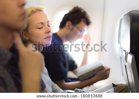 People flying by plane. Interior of airplane with passengers killing time on their seats. - stock photo
