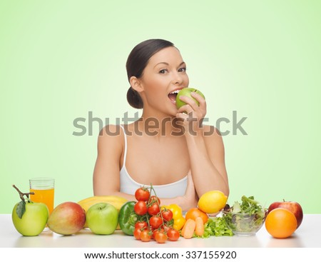 people, food, diet and weight loss concept - happy woman with fruits and vegetables eating apple over green background - stock photo