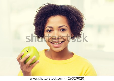 people, food, healthy eating and dental care concept - happy african american young woman with green apple at home - stock photo