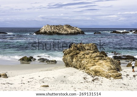 people, friends, young couple walking on the beach, climbing on rocks, enjoying time together - stock photo