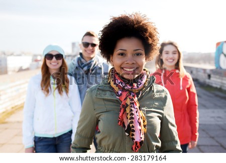people, friendship and international concept - happy african american young woman or teenage girl in front of her friends on city street - stock photo