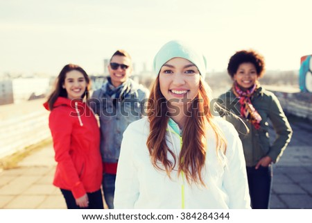 people, friendship and international concept - happy young woman or teenage girl in front of her friends on city street