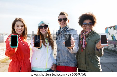 people, friendship, cloud computing, advertising and technology concept - group of smiling teenage friends showing blank smartphone screens outdoors - stock photo
