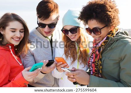 people, friendship, cloud computing and technology concept - group of smiling teenage friends with smartphone outdoors - stock photo