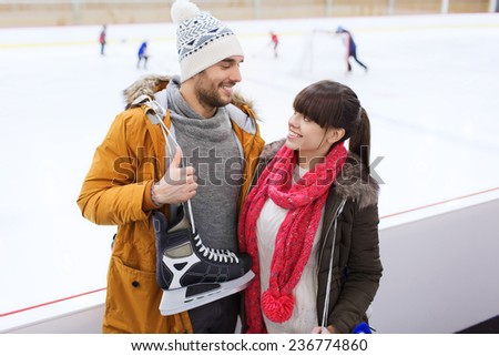 people, friendship, sport and leisure concept - happy couple with ice-skates on skating rink - stock photo