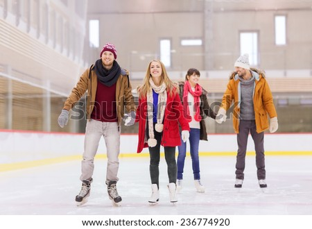 people, friendship, sport and leisure concept - happy friends on skating rink - stock photo