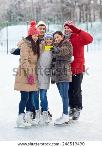 people, friendship, technology and leisure concept - happy friends taking selfie with smartphone on ice skating rink outdoors - stock photo