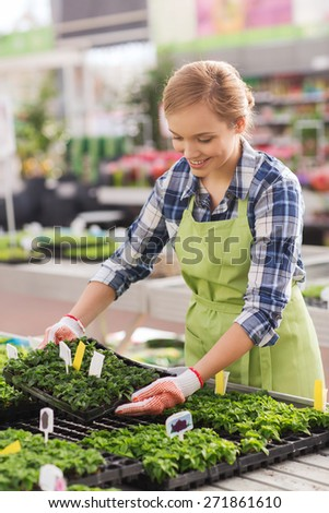 people, gardening and profession concept - happy woman or gardener taking care of seedling in greenhouse - stock photo