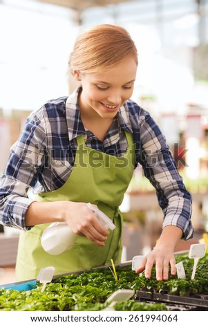 people, gardening and profession concept - happy woman or gardener with sprayer and seedling in greenhouse - stock photo