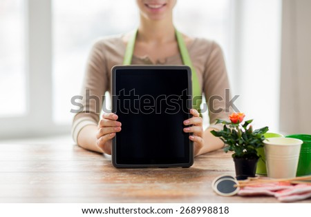 people, gardening, flowers and profession concept - close up of happy woman or gardener showing tablet pc computer black blank screen at home - stock photo