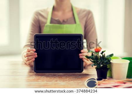 people, gardening, flowers and profession concept - close up of woman or gardener showing tablet pc computer black blank screen at home - stock photo