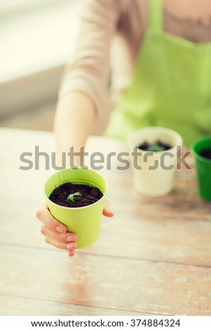 people, gardening, organic, planting and profession concept - close up of woman hand holding pot with sprout - stock photo