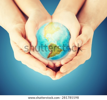 people, geography, population and peace concept - close up of woman and man hands with earth globe showing american continent over blue background - stock photo