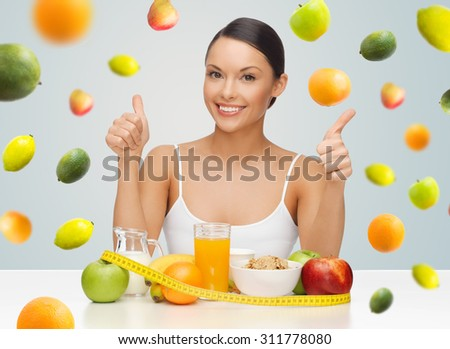 people, gesture and diet concept- happy asian woman with healthy food showing thumbs up over gray background with falling fruits - stock photo