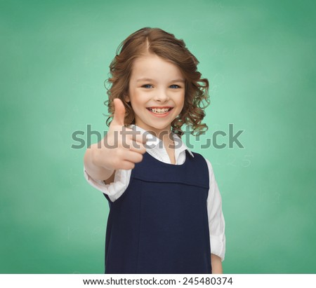 people, gesture, children, school and happiness concept happy little school girl showing thumbs up over green chalk board - stock photo