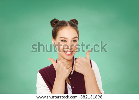 people, gesture, emotions, education and teens concept - happy smiling pretty teenage girl showing thumbs up over green school chalk board background - stock photo
