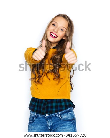 people, gesture, style and fashion concept - happy young woman or teen girl in casual clothes showing thumbs up - stock photo