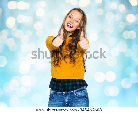 people, gesture, style and fashion concept - happy young woman or teen girl in casual clothes showing thumbs up over blue holidays lights background - stock photo