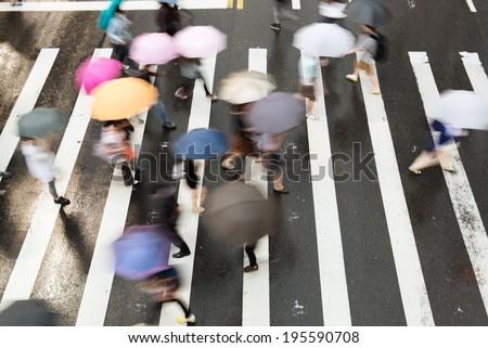 People go across the street in the rain. - stock photo