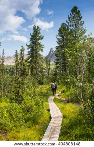 People go to the mountains, on a good  path - stock photo
