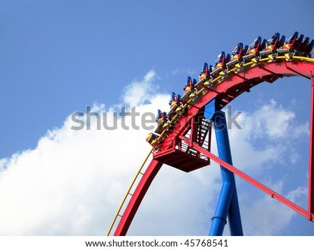 People going down on giant roller coaster ride, photo taken against bright blue sky and white cloud - stock photo