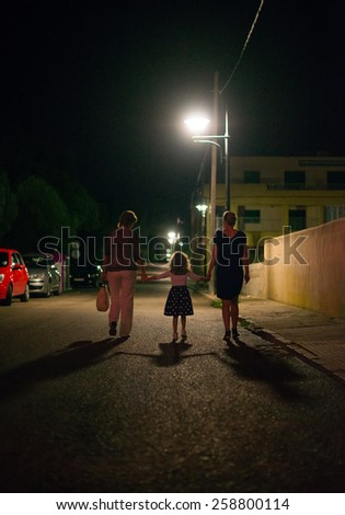 People going down the street at night. - stock photo