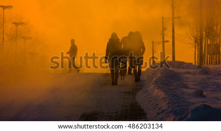 People going on the street in foggy evaporation at sunset, background
