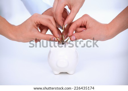 People hand putting coin into a piggy bank - stock photo