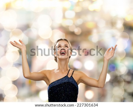 people, happiness, holidays and glamour concept - smiling woman raising hands and looking up over lights background - stock photo