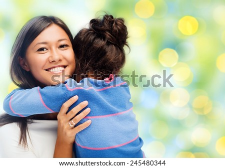 people, happiness, love, family and motherhood concept - happy mother and daughter hugging over green lights background - stock photo