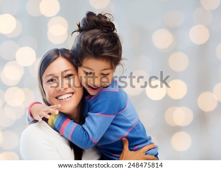 people, happiness, love, family and motherhood concept - happy mother and daughter hugging over holiday lights background - stock photo