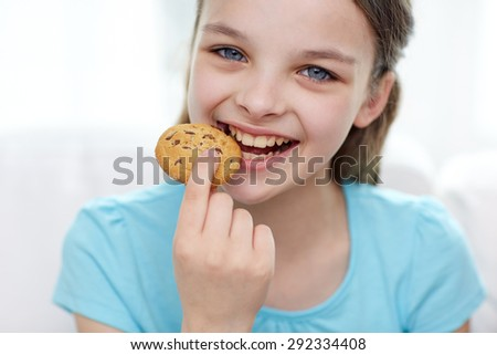 people, happy childhood, food, sweets and bakery concept - smiling little girl eating cookie or biscuit