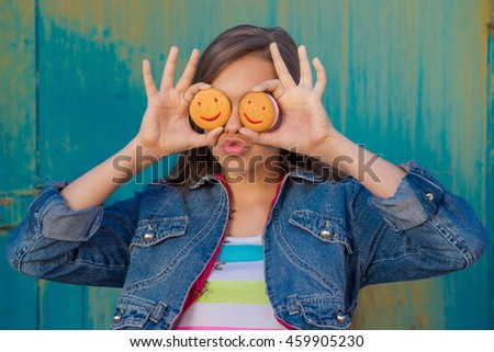 people, happy childhood, food, sweets and bakery concept - smiling little girl eating cookie or biscuit. Cheerful teen girl with cookies near the eye, smile biscuits  - stock photo