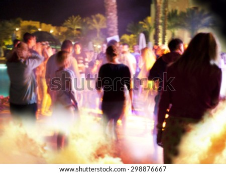People have fun at night on a beach. Blurry.