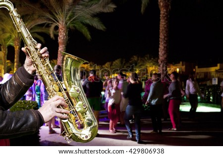 People have fun at night on a beach. Jazz.