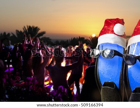 People have fun in Christmas night on the beach. Flippers. Sunglasses. Santa. humor. New Year.