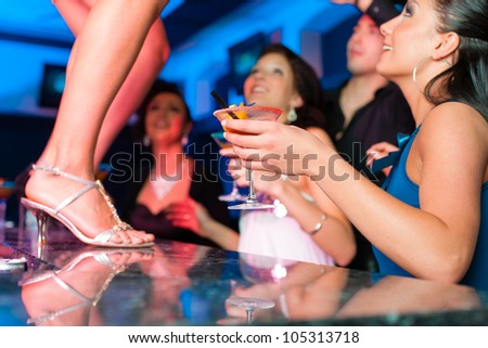 People having a party in club or bar, one woman is dancing on the table - stock photo